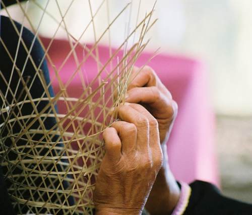 a woman from china weaves a basket at the Smithonian folklife festival in Washington DC (2007).